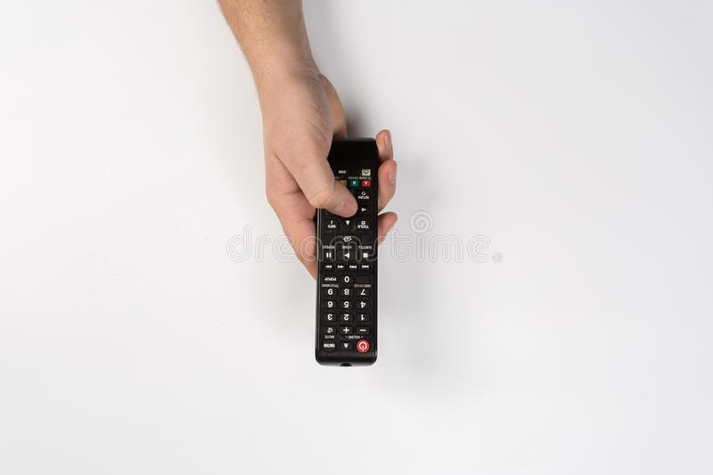 Hand with tv remote control isolated on white background stock photo