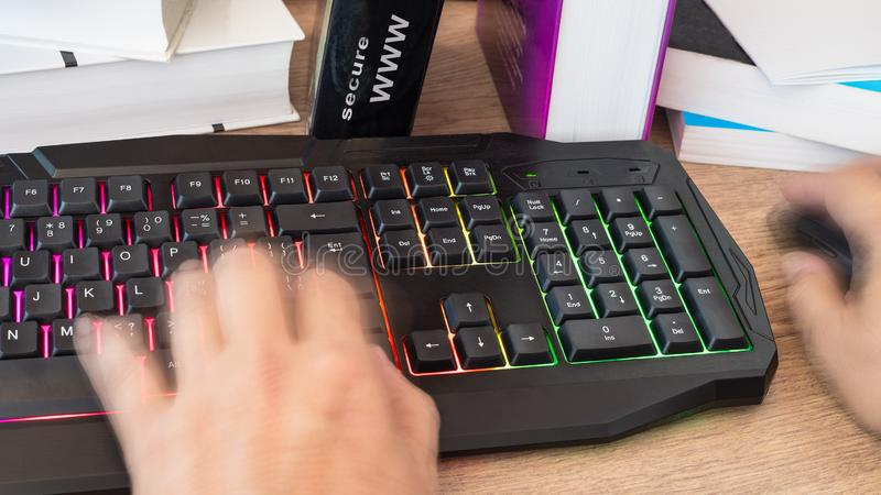 Hand typing on a colored keyboard. Motion blur stock photo