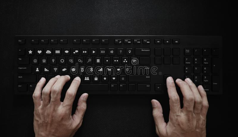 Hand typing on computer keyboard, with application icons on button. Application Programming Interface stock image
