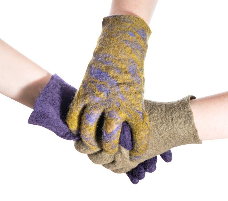 Hand umfasst Händedruck von Händen in farbigen Handschuhen lizenzfreies stockfoto