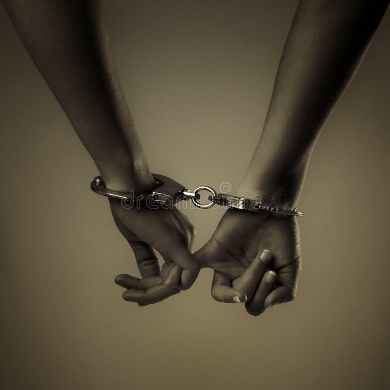 Hand und Handschellen mit zwei Mädchen stockbild