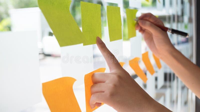 Hand unter Verwendung der klebrigen Anmerkung des Post-It mit Brainstorming lizenzfreie stockbilder