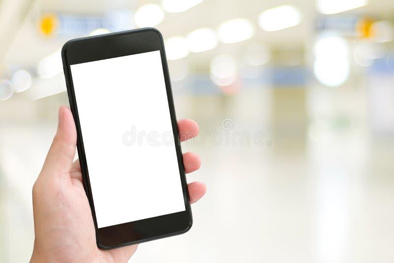 Hand unter Verwendung des intelligenten Telefons mit leerem Bildschirm über Unschärfe bokeh Licht b stockfotografie