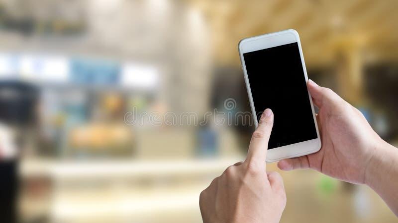 Hand unter Verwendung des leeren Schirmes von Smartphone für anwesende Anwendung an stockfotos