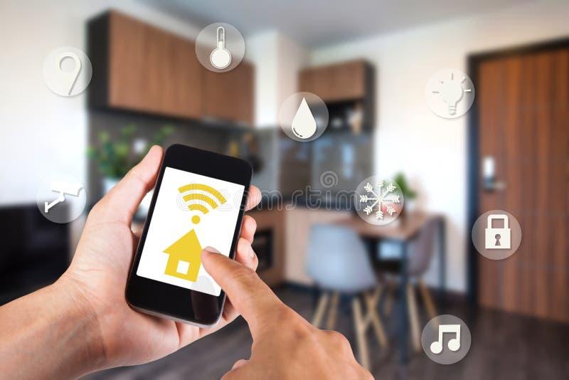 Hand unter Verwendung des Smartphone durch intelligentes Haus APP auf Mobile lizenzfreie stockfotografie