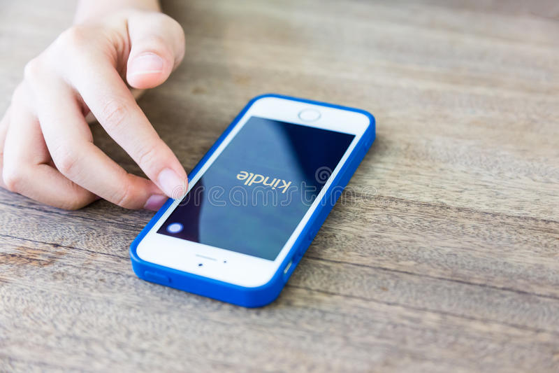 Hand unter Verwendung des Smartphone mit Kindle-APP, unter Verwendung der modernen Technologie lizenzfreies stockbild