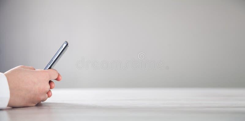 Hand unter Verwendung des Smartphone Moderner Schreibtisch technologie stockfotos