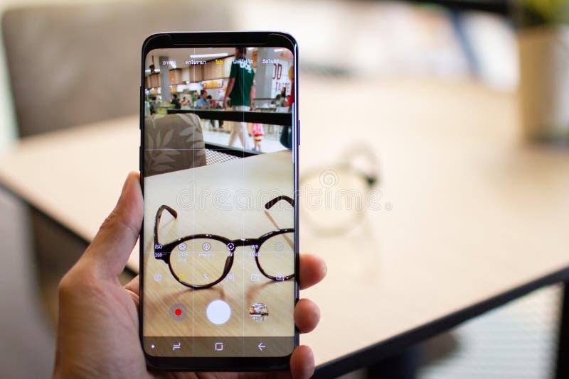 Hand unter Verwendung Handysamsungs-Galaxie s9+ am 26. April 2018, Thailand-Schießen Weinlese-Glasfoto lizenzfreie stockbilder