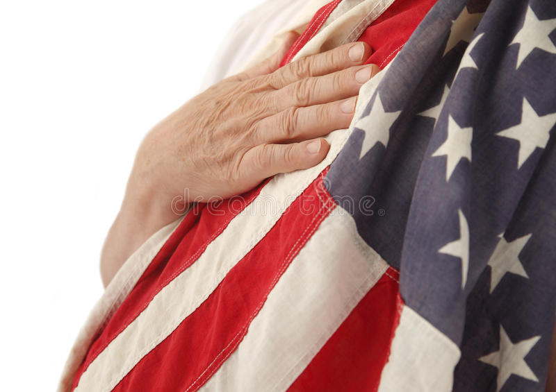Hand on USA flag. A man's hand on an old American flag draped over his shoulder stock image