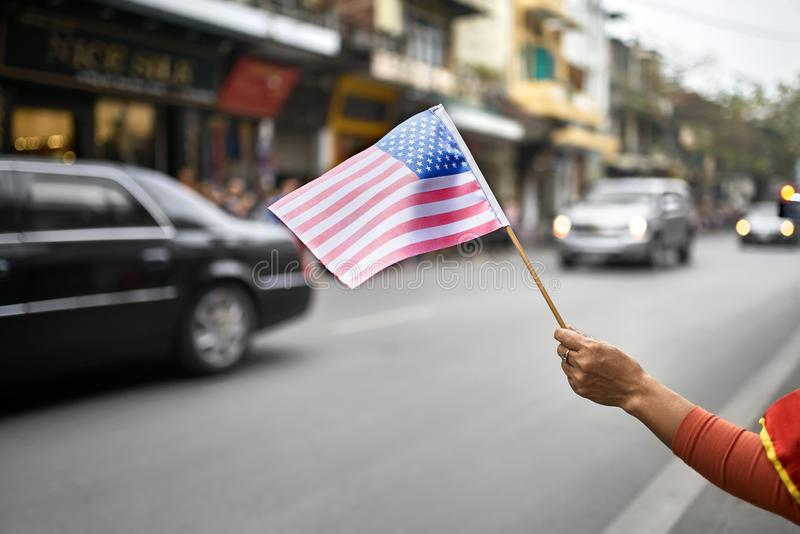 Citizen with flag welcomes diplomatic escort car passage. Hand with the USA flag on the blurred background of the moving cars of the american diplomatic escort royalty free stock images