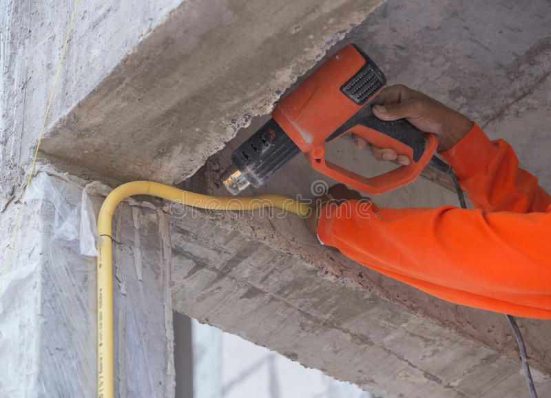 Hand use a heat gun to bending electric PVC pipe. Hand of worker use a heat gun to bending electric PVC pipe royalty free stock image