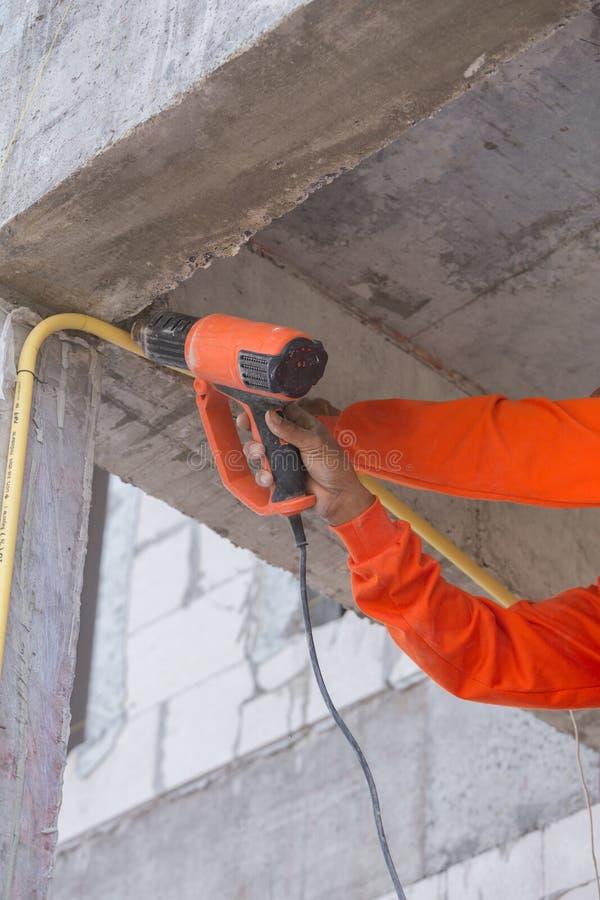 Hand use a heat gun to bending electric PVC pipe. Hand of worker use a heat gun to bending electric PVC pipe stock image