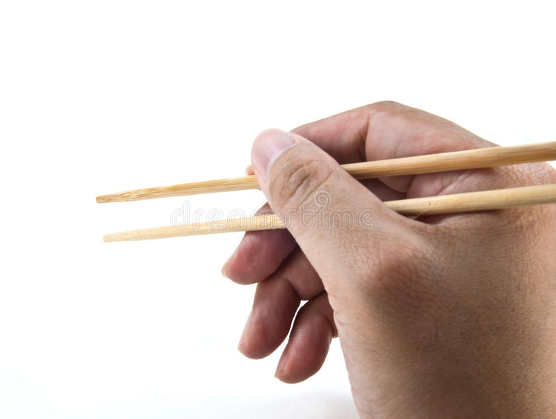 A hand using chopsticks. Shot on white background stock photography