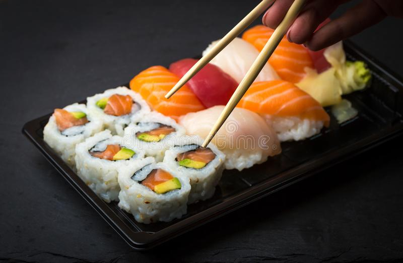Hand using chopsticks pick Sushi and Sashimi rolls on a black stone slatter. Fresh made Sushi set with salmon, prawns, wasabi and stock image