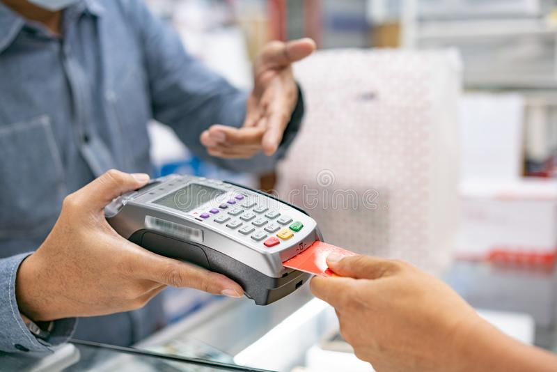 Hand using credit card swiping machine to pay. Hand with credit royalty free stock image