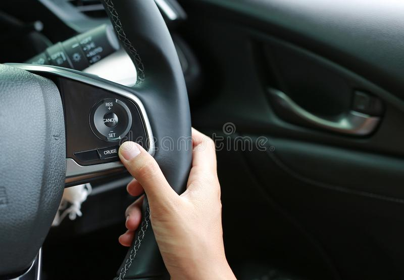 Hand using Cruise control buttons on modern car and speed limitation.  royalty free stock images
