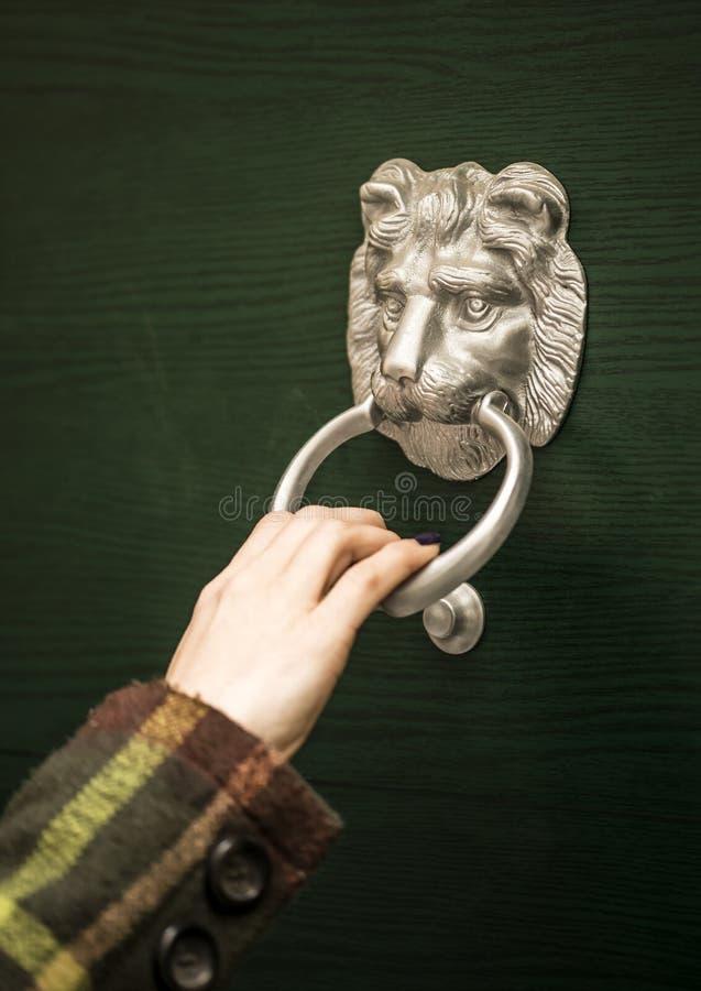 Hand using a door knocker. In lions head shape stock image