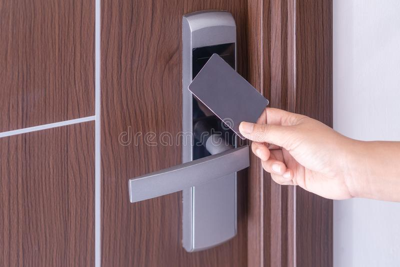 Hand using electronic smart contactless key card for unlock door in hotel or house royalty free stock image