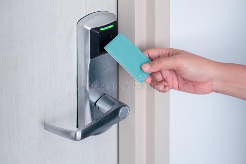 Hand using electronic smart contactless key card for unlock door in hotel or house royalty free stock images