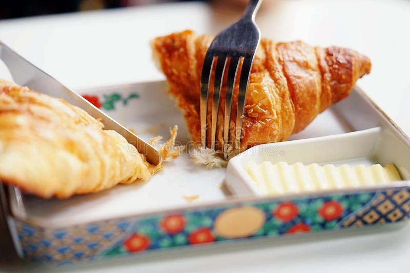 A hand are using fork and knife to eat of Blue cheese croissant served with butter. A restaurant scene for background stock photo