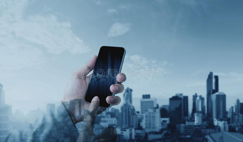 Hand using mobile smart phone with double exposure modern city background, Communication and network connection technology stock images