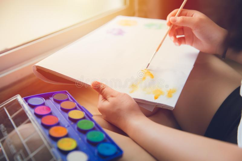 Hand using paint brush to draw water color painting for hobby at home royalty free stock images