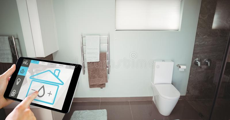 Hand using smart home application on digital tablet in washroom royalty free stock photos