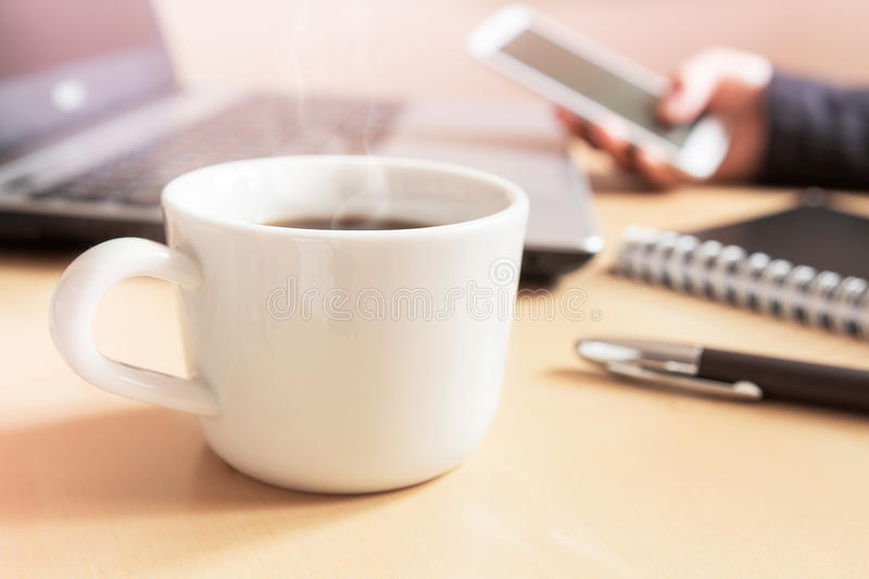 Hand using smartphone. Cup of coffee, notepad and laptop on the desk. Hand using smartphone. Cup of coffee, pen, notepad and laptop on the desk stock image
