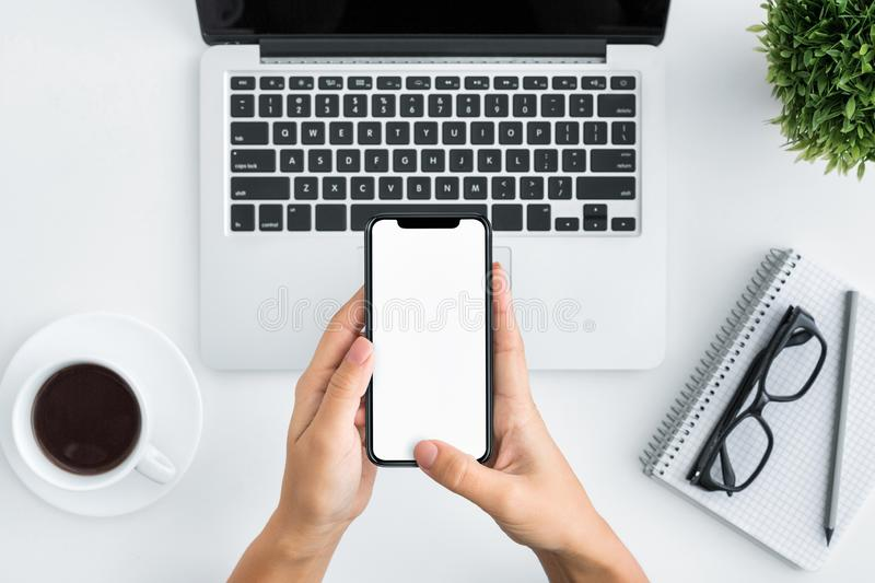Hand using smartphone on white wooden background royalty free stock photo