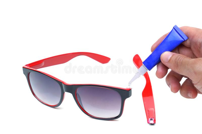 Repairing a pair of broken sunglasses. Hand using a superglue for repairing a pair of broken sunglasses isolated royalty free stock photos