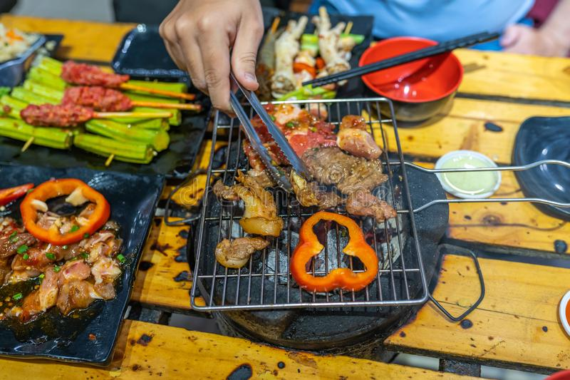 Hand holding tongs and grilling marinated meat and bell peppers. Hand using tongs and grilling marinated meat and bell peppers stock photos