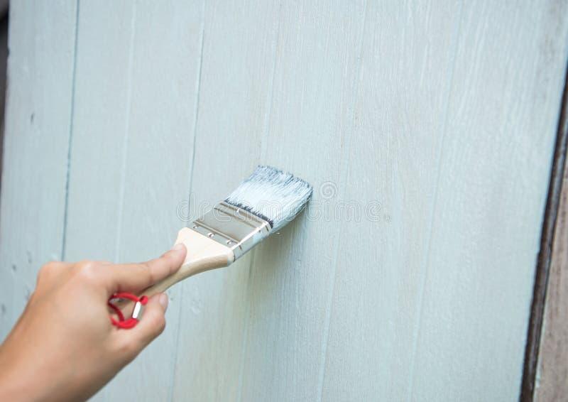 Hand van arbeider het schilderen op houten venster nieuw huis bij bouw royalty-vrije stock afbeelding
