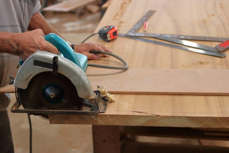 Hand van arbeiders scherp hout met elektrische cirkelzaag stock afbeelding
