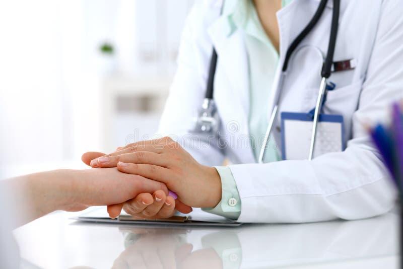 Hand van artsenvrouw het geruststellen aan vrouwelijke patiënt, close-up Medisch ethiek en vertrouwensconcept royalty-vrije stock foto's