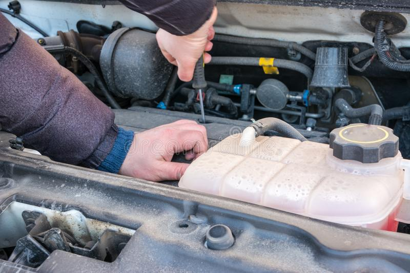 Hand van autowerktuigkundige met een schroevedraaier Autoreparatie stock foto