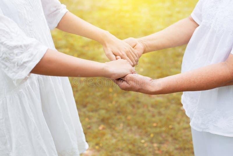 Hand van Aziatische vrouw die bejaarde handen houden terwijl het lopen bij openlucht, Ederly die zorgconcept nemen royalty-vrije stock afbeeldingen