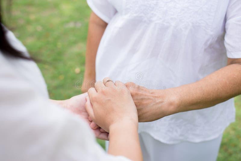Hand van Aziatische vrouwen die bejaarde handen houden terwijl het lopen bij park, Hoger nemend zorgconcept stock afbeelding
