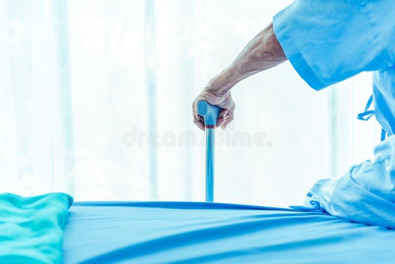 Hand van bejaarde met metaalwandelstok terwijl het zitten op bedpati?nt in het ziekenhuis Medische en gezondheidszorghuisbewaarde royalty-vrije stock fotografie