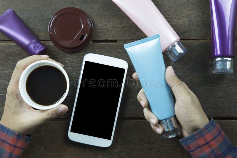Hand van de Aziatische mens die lege kosmetische buis en zwarte koffie p houden royalty-vrije stock afbeeldingen