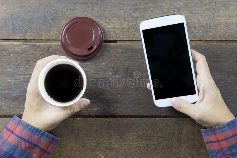 Hand van de Aziatische mens in lang overhemd die zwarte koffie houden royalty-vrije stock fotografie