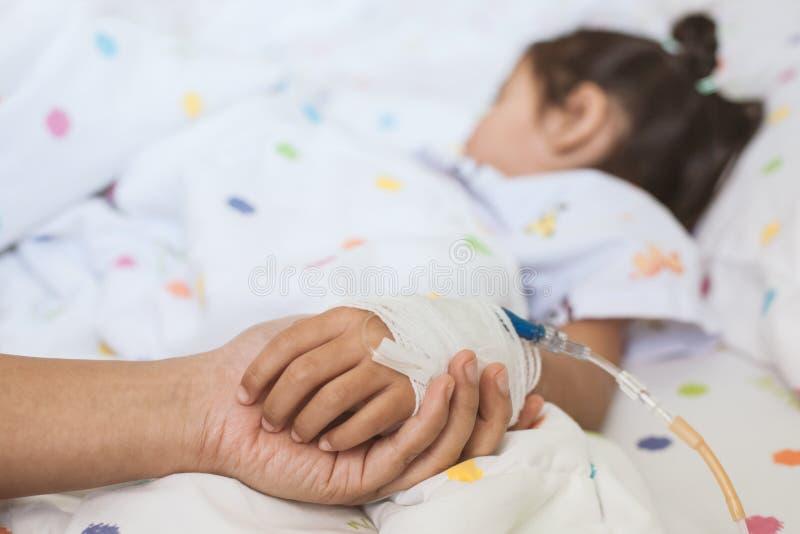 Hand van de de holdings de zieke dochter van de moederhand die IV oplossing hebben stock afbeeldingen