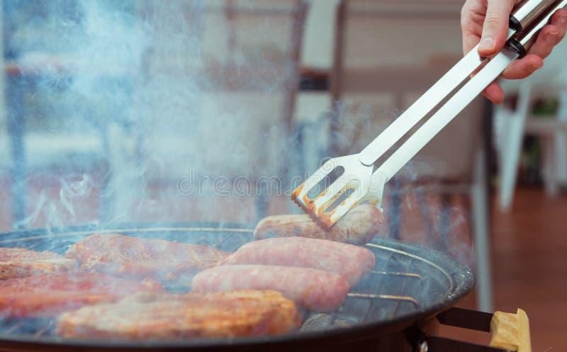 Hand van de jonge mens die wat lapje vlees, worst bij de grill roosteren stock afbeeldingen