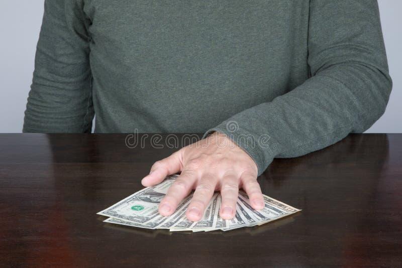 Hand van de mens die een bundel van dollars houden stock foto's
