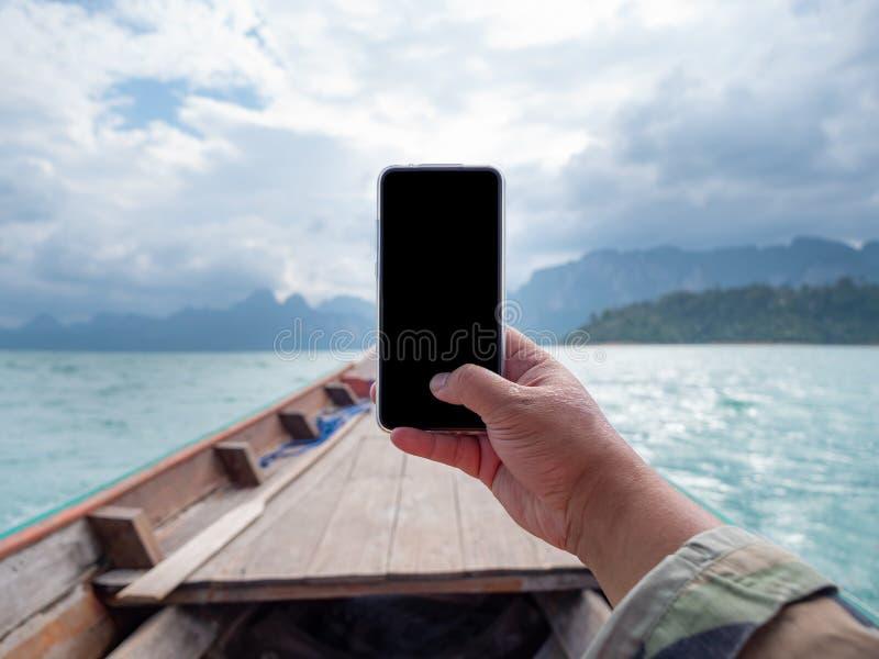 Hand van de mens die mobiele smartphone met behulp van tegen toneellandschap van bootmening in de grote rivier en reservoirdam me stock afbeelding