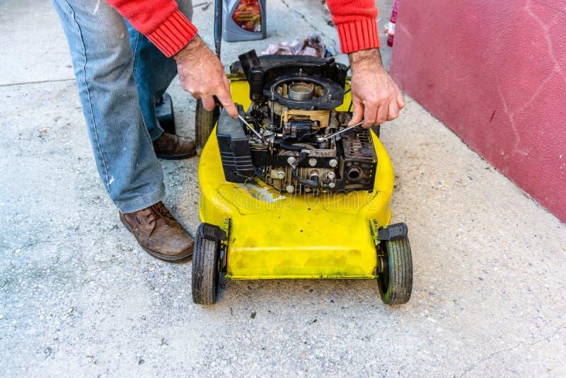Hand van de mens die oude grassnijder met hulpmiddelen op cementvloer herstellen Het herstellen van grasmaaimachinemotor royalty-vrije stock fotografie