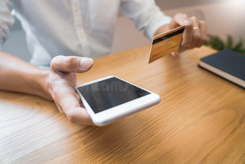 Hand van de mens in toevallig overhemd die met creditcard betalen en smartphone met behulp van voor online het winkelen makend or stock foto