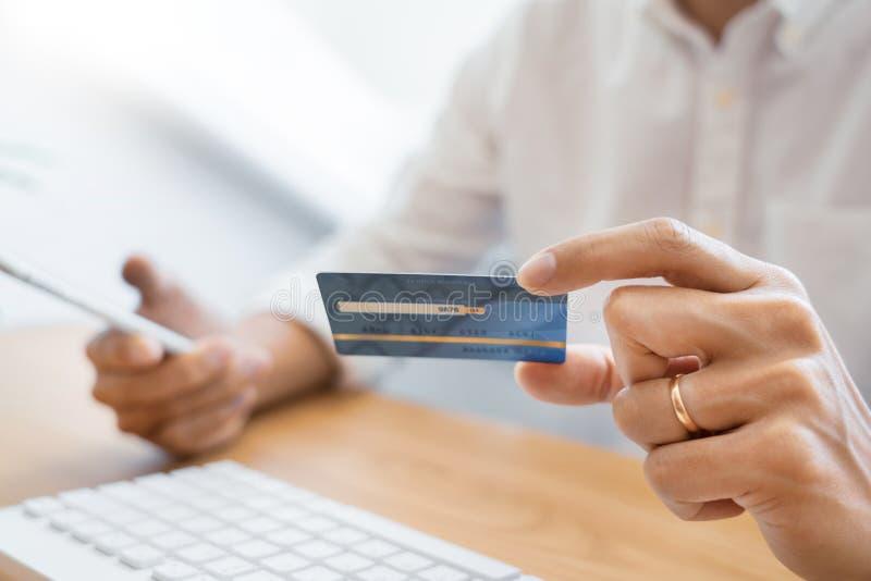 Hand van de mens in toevallig overhemd die met creditcard betalen en smartphone met behulp van voor online het winkelen makend or stock afbeelding