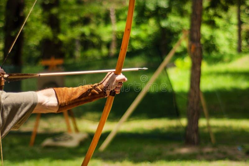 Hand van de mensen houdt de middeleeuwse schutter zijn boog met een pijl en het streven naar het doel stock afbeelding