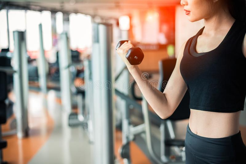 Hand van de opheffende domoor van de sportenvrouw voor gewichtheffen met de hand voor het pompen van bicepsenspier met fitness gy royalty-vrije stock afbeelding