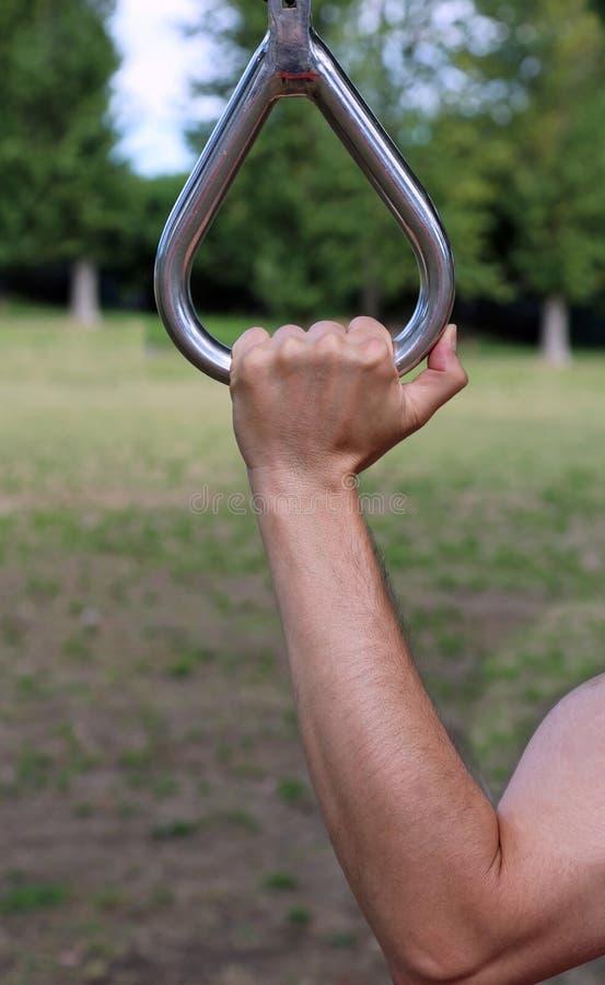 Hand van de spieratleet die stevig de gymnastiek- ring grijpt stock fotografie